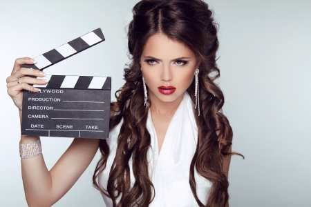 Fashion woman with sexy red lips holding cinema clap. Super star model shot photo