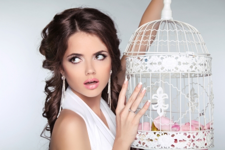 Concept photo of amazed woman holding vintage bird cage isolated on grey background photo