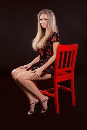 Beautiful woman with long sexy legs sitting on red chair isolated on a black background photo
