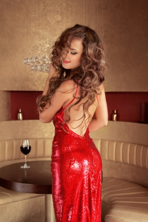 alluring: Beautiful elegant woman wearing in red dress posing in luxurious classic interior.