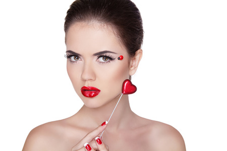 Beautiful face woman with glamour bright makeup holding heart. Trendy Red Manicure and Red Lips. Fashion Make-up and Manicure. Stock Photo - 22348710