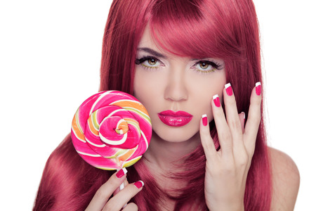 Beauty Girl Portrait holding lollipop with Colorful Makeup, Coloring Pink Hair, Manicured nails.  photo
