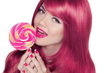 Happy smiling teen girl holding multicolored lollipop with pink long glossy hair style. Isolated on a white Background. photo