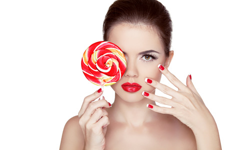 Fashion makeup. Beauty Girl Portrait holding Colorful lollipop. Hot red lips. Nail polish manicured nails. Skin care. Isolated on white background photo