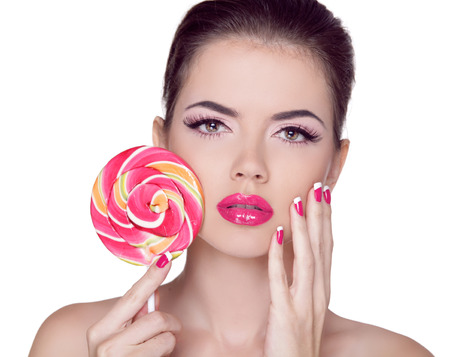 Bright makeup. Beauty Girl Portrait holding Colorful lollipop. Pink Lips. Nail polish manicured nails. Skin care photo
