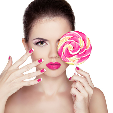 Beauty Girl Portrait holding Colorful lollipop. Fashion makeup. Nail polish manicured nails. Skin care. Isolated on white background. Colourful Studio Shot of Funny Woman. photo