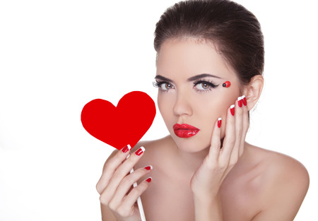Beautiful woman with glamour bright makeup holding red heart isolated on white background. Manicured nails and Red Lips. Valentines Day  photo