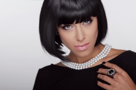 Vogue style. Fashion Haircut. Hairstyle. Sexy Lady. Stylish Fringe. Short Hair Style. Brunette woman with jewelry pearls
