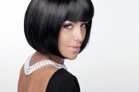 a bob: Corte de pelo de moda. Peinado. Se�ora atractiva. Fringe estilo. Estilo de pelo corto. Mujer morena con perlas de joyer�a Foto de archivo