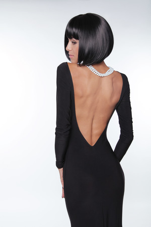 back straight: Brunette woman with sexy back in black dress posing at studio. Vogue style. Fashion Haircut.