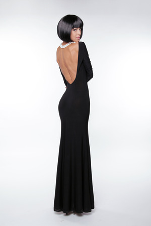 Brunette woman with sexy back in black long dress posing at studio. Vogue style. Fashion Haircut.  photo