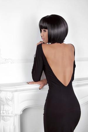 detras de: Style Vogue. Belleza de mujer de moda en el vestir sexy que muestra de nuevo. Virgen Morena con Negro Corto Estilismo posando detrás de la pared moderna.
