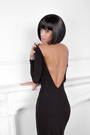 hair back: Vogue Style. Fashion Beauty Woman in sexy dress showing back. Brunette Lady with Black Short Hair Styling posing behind modern wall.