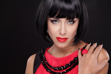 Fashion Brunette Woman Portrait with Red Lips isolated on a black background. Showing ring Stock Photo - 22615402