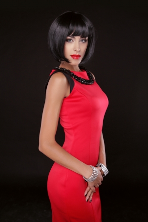 Fashion Elegant Woman in red dress. Brunette Lady with Black Short Hair. Vogue Style. Model posing isolated on black background at studio.  photo