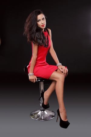 Sexy young gorgeous brunette woman in red dress on the chair, isolated on black, studio shot. Stock Photo - 22615406
