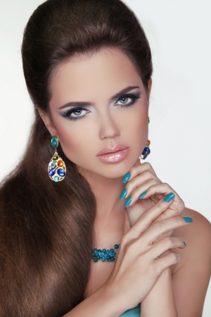 Portrait of beautiful woman with bright fashion makeup and brown hair styling. Showing jewelry. Stock Photo - 22578781