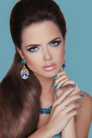 Jewelry. Portrait of young beautiful girl with blue eyes. Fashion photo of woman model isolated on blue background. 스톡 콘텐츠