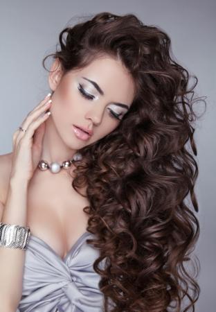 Wavy Hair. Beautiful Sexy Brunette Woman. Healthy Long Brown Hair. Beauty Girl. Fashion model posing at studio. Stock Photo