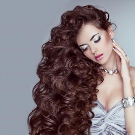 Porträt einer schönen Frau mit langen gewellten Haar posiert auf grauem Hintergrund Standard-Bild - 22616813