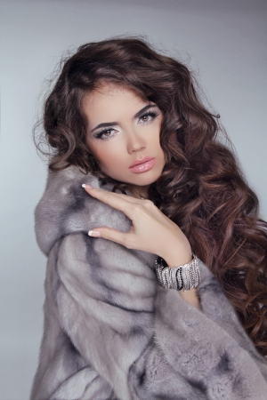 wavy hair: Beautiful brunette girl wearing in mink fur coat with long hair styling isolated on grey background. Fashion winter woman model posing.