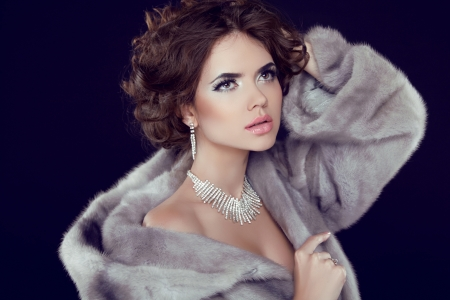 Fashion Model Girl Portrait with jewelry wearing in grey mink fur coat isolated on black background.