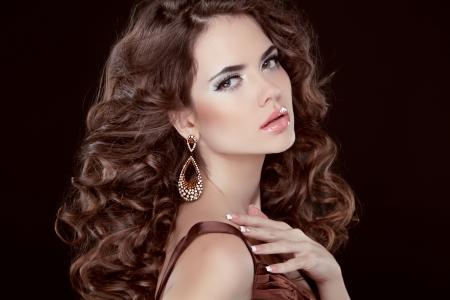 Cheveux ondulés. Belle femme brune sexy. Santé longs cheveux bruns. Beauté fille modèle. Boucle d'oreille. Studio photo Banque d'images