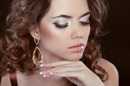 Earrings. Beauty Woman With Long Brown Curly Hair. Hairstyle. Beautiful Model Girl Portrait. Accessory photo
