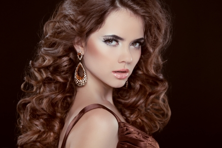 Beauty Portrait. Hairstyle. Brunette woman with Long Healthy Brown Hair isolated over dark background. Elegant lady