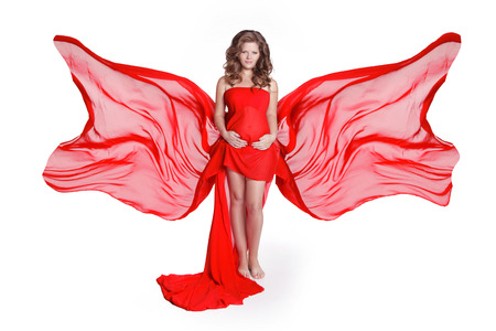 Beautiful woman stroking her belly in blowing red fabric dress isolated on white background. Studio Photo Stock Photo - 22626893