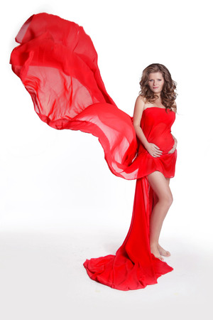 Beautiful woman stroking her belly in blowing red fabric dress isolated on white background. Studio Photo Stock Photo - 22649276