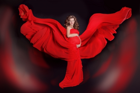 Beautiful Pregnant woman with red blowing tissue over dark background. Art photo Stock Photo - 22649279