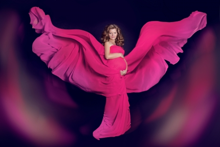 Art photo. Beautiful Pregnant woman with colored blowing tissue wings over dark background. Stock Photo - 22649280