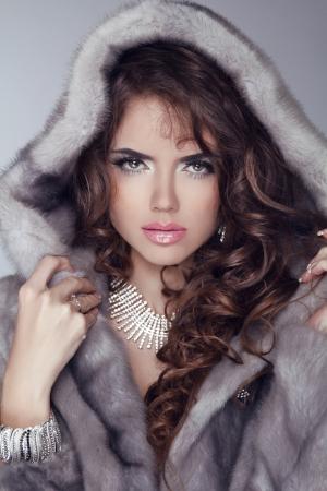 Bellezza moda modello donna in pelliccia di visone. Winter Girl in abiti di lusso e lunghi capelli ondulati. Modello in posa