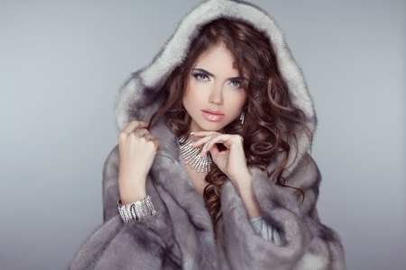 Fashion beautiful woman posing in fur coat. Winter Girl  Model in Luxury clothes and snowy furry hood Isolated on gray background.