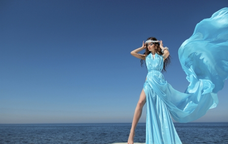Luxury life. Fashion model girl with blowing tissue dress over blue sky, outdoors.  photo