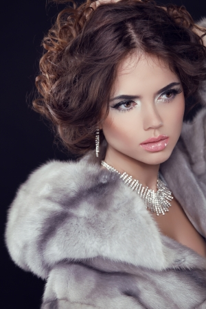 necklaces: Winter Fashion. Beautiful Sexy Brunette Woman wearing in Luxury Mink Fur Coat isolated black background.