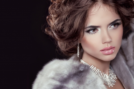 bangle: Glamour. Fashion girl Model wearing in Luxury Mink Fur Coat isolated black background.
