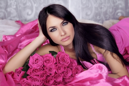 Beauty portrait of brunette girl with pink Roses lying on the bed. Luxury Woman with Blue Eyes and long black hair. Passion