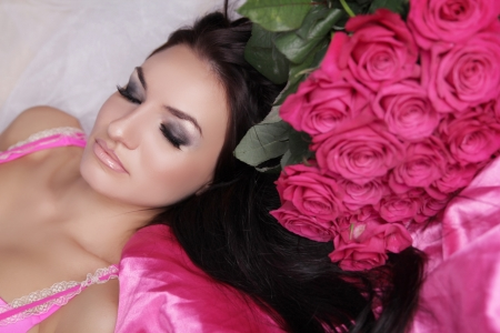 Enjoyment. Treatment. Beauty Model Woman Face. Beautiful Girl With Roses Flowers. Perfect Skin. Professional Make-up.  photo