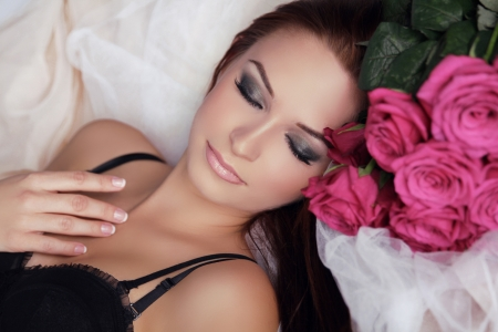 Beautiful Girl With Roses Flowers. Beauty Model Woman Face. Perfect Skin. Professional Make-up. Relax. photo