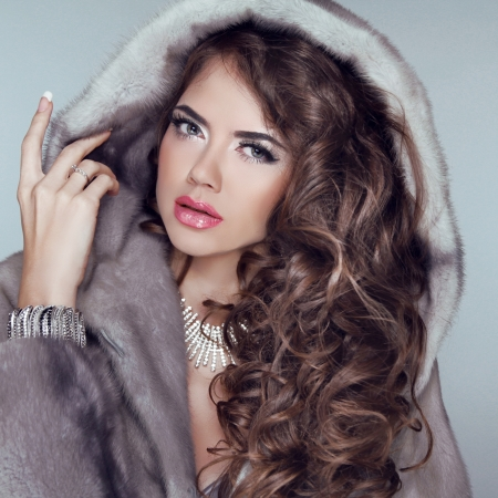 wavy hair: Beautiful brunette girl wearing in mink fur coat with long hair styling isolated on grey . Fashion winter woman model posing. Stock Photo