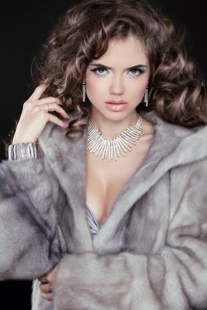 Fashion winter woman model wearing in mink fur coat with long wavy hair styling. Jewelry. Luxury life. Stock Photo - 24106299
