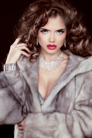 Beautiful brunette girl wearing in mink fur coat with long wavy hair styling. Jewelry. Fashion winter woman model posing. Stock Photo - 24106300