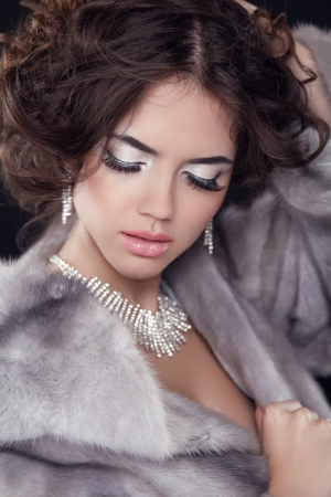 Portrait of the beautiful fashion woman wearing in mink fur coat with wavy hair styling. Jewelry accessories.  Stock Photo - 24106302