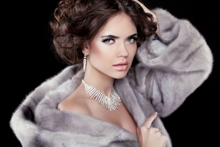 Portrait of the beautiful fashion woman wearing in mink fur coat with wavy hair styling. Jewelry accessories.  photo