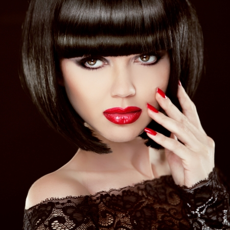 Portrait of Sexy brunette woman with short black hair, red lips, manicured polish nails. Makeup. Hairstyle. Isolated on dark Stock Photo - 24106310
