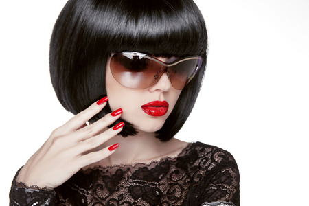 Fashion portrait of a beautiful brunette woman with shot hairstyle with red sunglasses. Red lips. Manicured nails.Isolated on white . Studio photo Stock Photo - 24106318