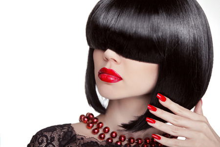 Sexy Glamour Girl. Fashion portrait of brunette woman with black hair showing red manicured polish nails and hot lips. Professional makeup and hairstyle. Model isolated on white . Stock Photo - 24106320