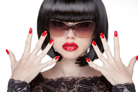 Fashion portrait of brunette woman in sunglasses showing red manicured polish nails. Professional makeup and hairstyle. Model isolated on white . Stock Photo - 24106328